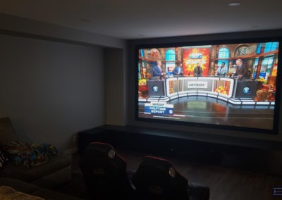 """Home Theatre Design and Installation. Projector and 120"""" acoustic transparent Screen Installation, Concealed Wiring, Dolby Atmos In-wall and In-ceiling Surround Sound Installation. Elevated theatre seating. Residential Basement. London, Ontario -HTAV."""