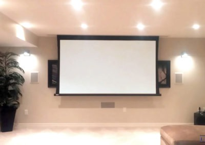 """Home Theatre Design and Installation. Projector and Screen Installation, Concealed Wiring, In-wall and In ceiling Surround Sound Installation. 120"""" recessed powered screen with BenQ projector and Marantz receiver powering a Dolby Digital 7.1 in-wall and in-ceiling surround sound speaker system. Residential Basement. London, Ontario -HTAV."""